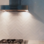 herringbone backsplash with alternating rows of glossy and matte tile