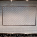 glass tile backsplash with herringbone insert and Schluter frame