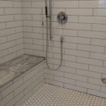 long subway tile in shower with mosaic hex floor and bench