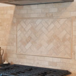 natural stone backsplash with herringbone insert over stovetop
